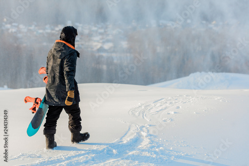 Tuinposter Wintersporten back view photo. sporty man with a snowboard going for a walk. copy space. man has finished to snowboard