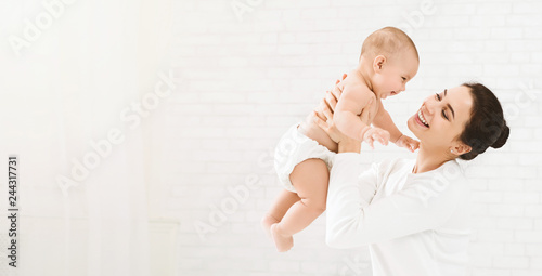 Fototapeta Young mom holding her happy baby in air obraz