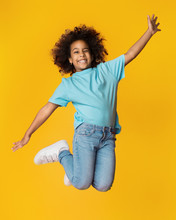 Little African-american Girl Jumping Over Studio Background