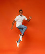 canvas print picture - Excited african-american man jumping on orange background