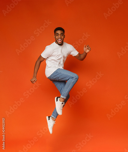 Photo  Excited african-american man jumping on orange background