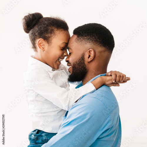 Fotografía  Father hugging with daughter, touching foreheads in studio