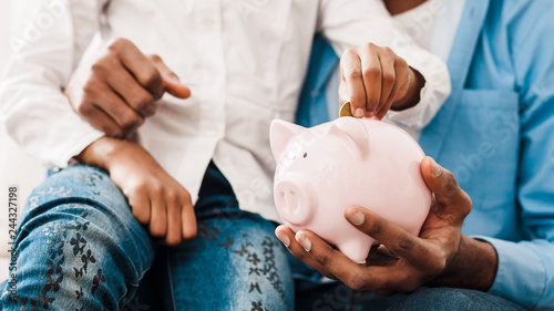 Fototapeta Dad and daughter saving money to piggy bank