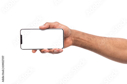 Male hand holding smartphone in horizontal orientation