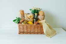 Italian Food Basket With Bread, Basil, Olive Oil, Lemons, And A Bottle Of Wine.