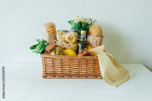 Italian food basket with bread, basil, olive oil, lemons, and a bottle of wine Fototapete