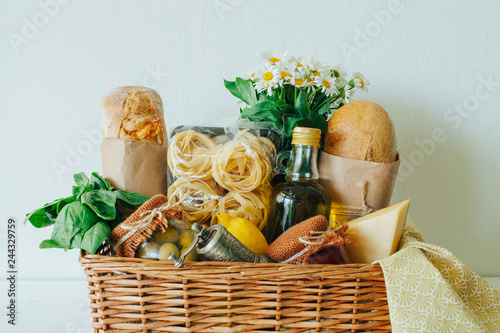 Leinwand Poster Italian food basket with bread, basil, olive oil, lemons, and a bottle of wine