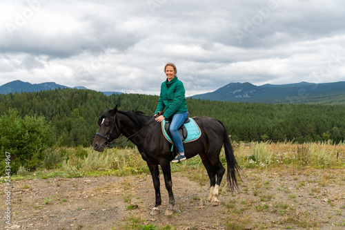 Poster Equitation Beautiful girl on the background of a small lake and a big mountain. Incredible beauty landscape