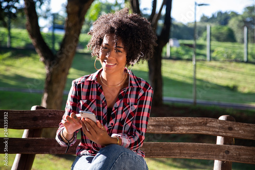 Photo  Portrait of a young african american woman listening to music on cell phone - Im