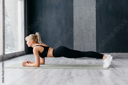 Athletic woman doing plank exercise in white sunny gum Slika na platnu