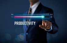 Increase Productivity Concept. Businessman Is Pulling Up Progress Bar With The Word PRODUCTIVITY On Dark Tone Background.