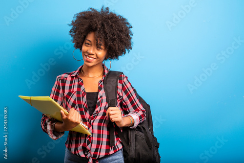Fotografia  young african student with backpack on the back on blue background