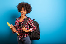 Young African Student With Backpack On The Back On Blue Background