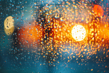 Headlights through glass with rain drops. Blur bokeh, defocused background