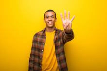 Young African American Man On Vibrant Yellow Background Happy And Counting Four With Fingers