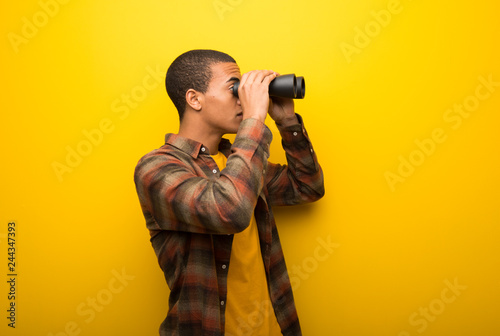 Young african american man on vibrant yellow background and looking for somethin Canvas Print