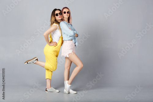 Photo  Shot of cheerful young female best friends in sunglasses with pleasant appearance and broad smiles in stilysh color jeans casual clothes having fun over gray background
