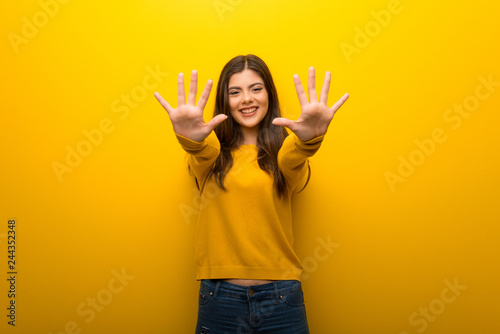 Fényképezés  Teenager girl on vibrant yellow background counting ten with fingers