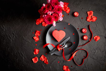Valentines Day, Table Setting And Romantic Dinner Concept. Close Up Of Plate With Cutlery And Rose Petals On Black Stone Background
