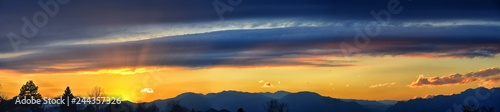 Tranquil panoramia scene of red sun and orange sky sunset over the Rocky Mountains in Colorado by Denver, United States.