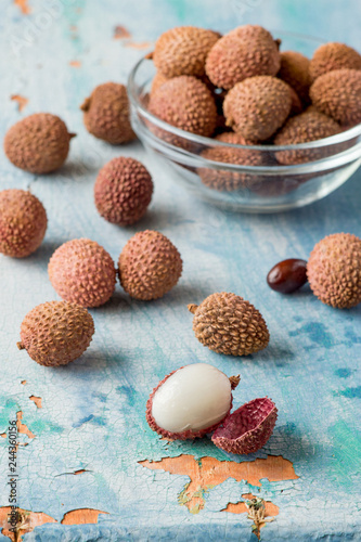 Ripe lychee fruits on an old wooden table.