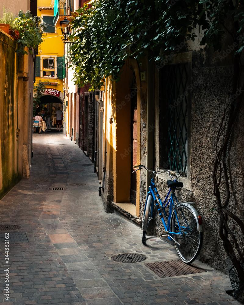Stary rower opiera się o ścianę w bocznej uliczce w Gardzie, Włochy <span>plik: #244362162   autor: Mike</span>