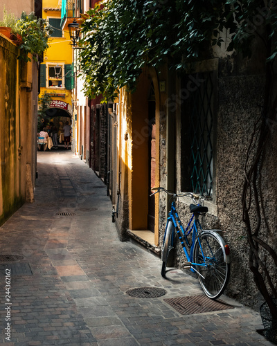 An old bike rests against a wall in a side street in Garda, Italy