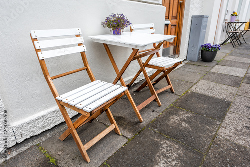 Foto  White empty wooden table outside restaurant cafe with two chairs on sidewalk str