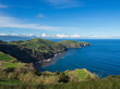 green fields pasture and coastal cliffs and blue ocean and sky horizon at north coast of sao miguel island, Azores, Portugal