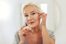 Positive Joyful Woman Applying Eye Patches On The Face