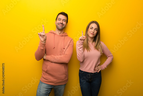 Photographie  Group of two people on yellow background showing and lifting a finger in sign of