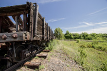 Abandoned Mine Carts. Weathered Abandoned Wooden Mine Cars On Rusty Railroad Tracks In An Empty Barren Landscape.