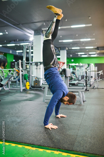 Strong skilled young bearded man  with prosthetic leg keeping balance while stan Fototapet