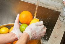 Citrus Fruits Washing In A Sink. Water Splashing On Lemon. Chef Washing Orange, Lemon And Lime Under Tap Water.