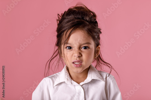 Valokuvatapetti angry little child girl in white shirt with hairstyle