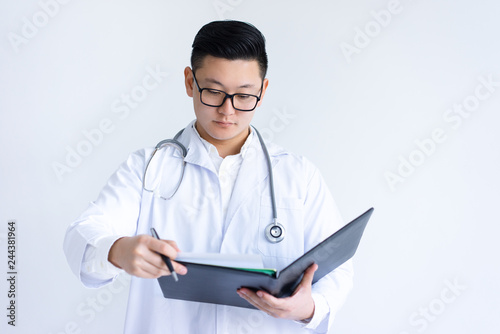 Photo  Serious young Asian male doctor working with documents