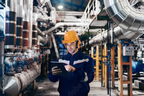 Valokuvatapetti Portrait of young Caucasian man dressed in work wear using tablet while standing in heating plant