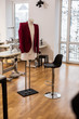 Elegant red jacket for women hanging on a dummy in a fashion studio