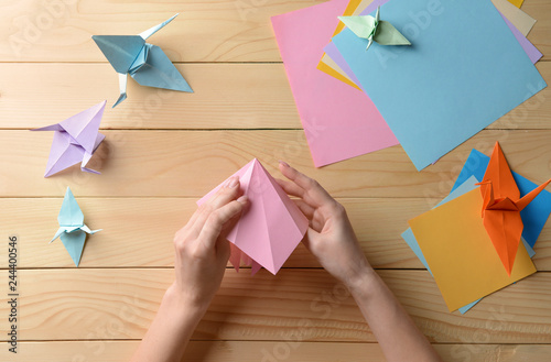 Young woman making origami on wooden table Wallpaper Mural