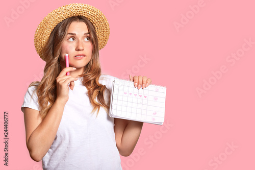 Fotografía  Horizontal shot of pleasant looking woman with thoughtful expression, wears head