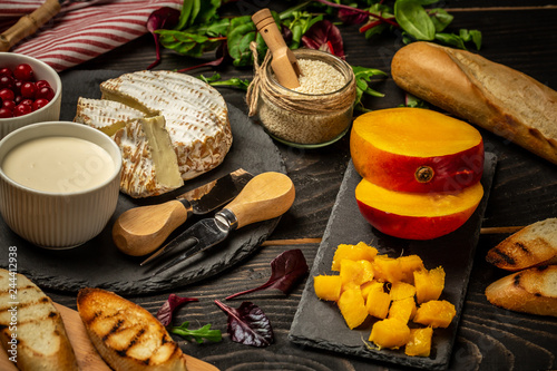 Aluminium Prints Picnic Variety of fresh food ingredients for Bruschetta with chopped mango, cream cheese on fresh baguette on the table