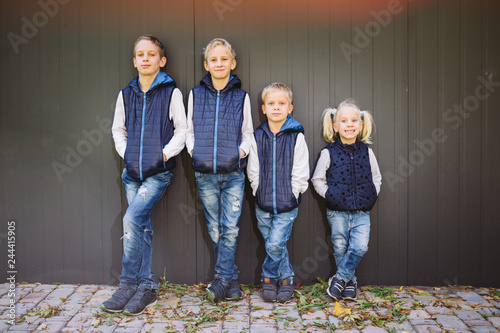 Obraz Funny Caucasian big family of three brothers and sister posing standing on growth background of wall in full growth. Equally stylishly dressed in blue vests and jeans. Theme girl in male circle - fototapety do salonu