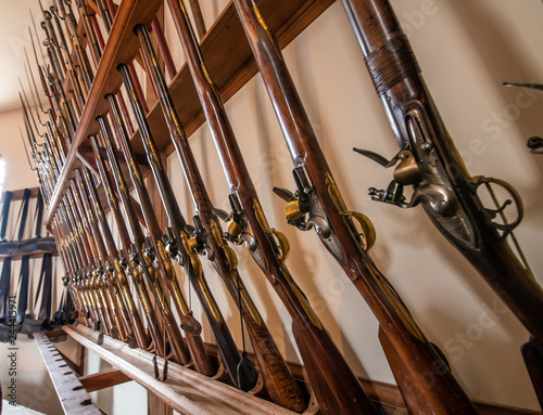 A row of old vintage antique muskets in a row in an armory Wallpaper Mural