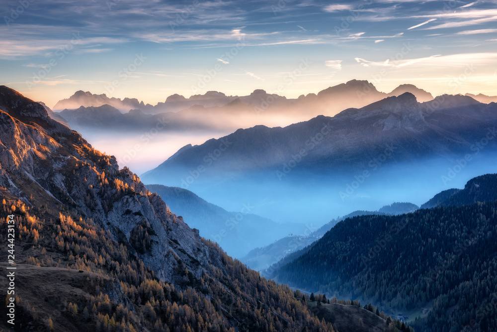 Fototapety, obrazy: Mountains in fog at beautiful sunset in autumn in Dolomites, Italy. Landscape with alpine mountain valley, low clouds, trees on hills, village in fog, blue sky with clouds. Aerial view. Passo Giau