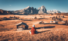 Sitting Woman On The Hill Looking On Meadows And Mountains At Sunset In Autumn. Alpe Di Siusi, Dolomites, Italy. Landscape With Girl In Red Jacket, Field With Orange Grass, Wooden Houses And Rocks