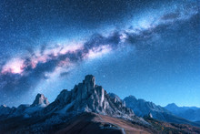 Milky Way Above Mountains At Night In Autumn. Landscape With Alpine Mountain Valley, Blue Sky With Milky Way And Stars, Buildings On The Hill, Rocks. Aerial View. Passo Giau In Dolomites, Italy. Space