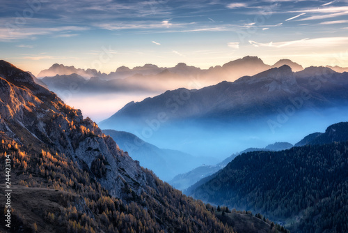 Fototapeta Mountains in fog at beautiful sunset in autumn in Dolomites, Italy. Landscape with alpine mountain valley, low clouds, trees on hills, village in fog, blue sky with clouds. Aerial view. Passo Giau obraz