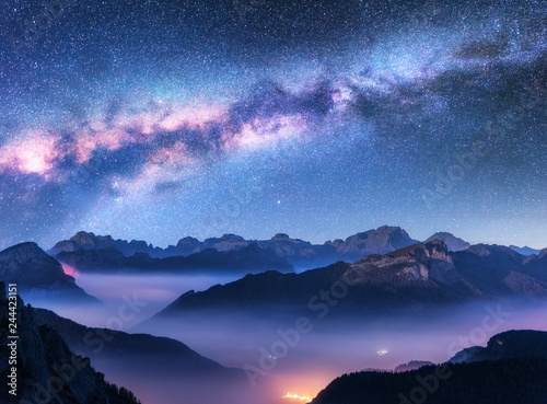 Spoed Foto op Canvas Nachtblauw Milky Way above mountains in fog at night in autumn. Landscape with alpine mountain valley, low clouds, purple starry sky with milky way, city illumination. Aerial. Passo Giau, Dolomites, Italy. Space
