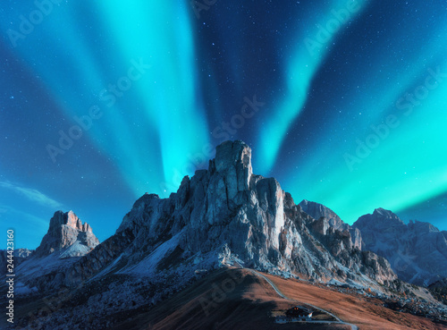 Poster Aurore polaire Northern lights above mountains at night in Europe. Aurora borealis. Starry sky with polar lights and high rocks. Beautiful landscape with aurora, road, buildings on the hill, mountain ridge. Travel