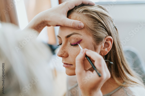 Makeup artist doing a wing liner for the model Canvas Print